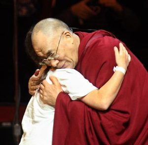 The Dalai Lama gives Jessica Markowitz, a 7th-grader at Seattle Girls' School, a hug during the KeyArena event.