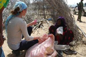 """Amanda Lindhout, in Somalia, talks with Sameya Mohamed, who thanked her for bringing food and said, """"my grandchildren are starving."""" (Kate Snow)"""
