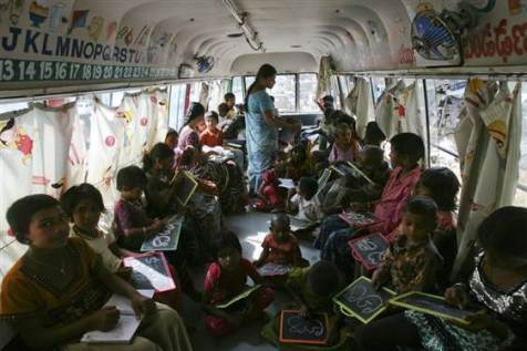 Children write letters from the Telugu alphabet as a teacher conducts lessons inside a bus converted into a school at a slum in the southern Indian city of Hyderabad.