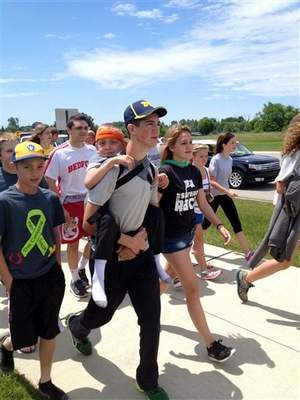 Hunter Gandee, 14, walks in Saline, Mich., on Sunday, June 8, 2014, during the second day of his two-day, 40-mile trek. Titled the Cerebral Palsy Swagger, the walk hoped to raise awareness for the muscle disorder that affects his 7-year-old brother, Braden, who was on his brother's back for the entirety of their journey from Temperance, Mich., to Ann Arbor, Mich. (AP Photo/Mike Householder) / AP